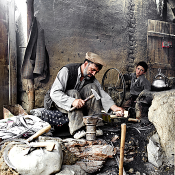 Blacksmith works the metal whilst son turns the wheel to keep the furnace burning Kabul